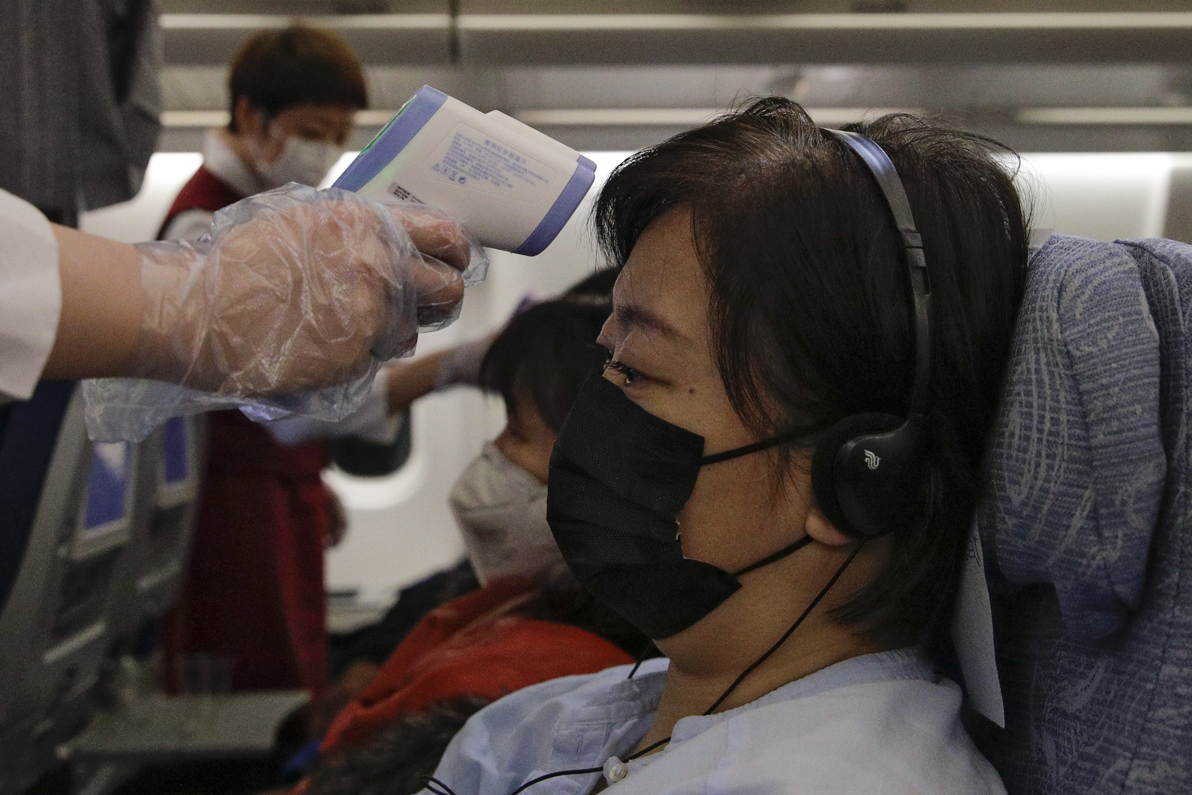 Flight attendants check temperatures of passengers aboard an Air China flight from Melbourne to Beijing on Feb. 4, 2020. AP Photo/Andy Wong