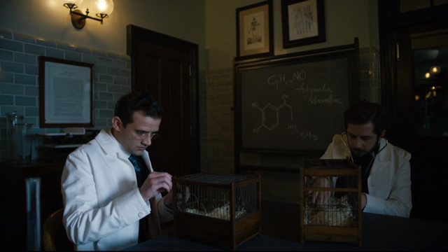 "Dr. Bertrand Chickering, Jr. (right) runs into a little conflict by wanting to move too fast for his new team and is told, ""Dr. Zinberg is very specific about his protocols. Start on mice. Present our findings. Then on to rats, then guinea pigs, then cats, dogs, and pigs, and only then to humans."""