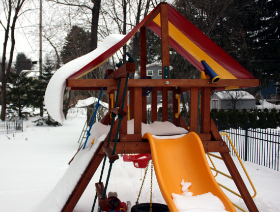 Snow hanging off the edge of SteelyKid's playset.