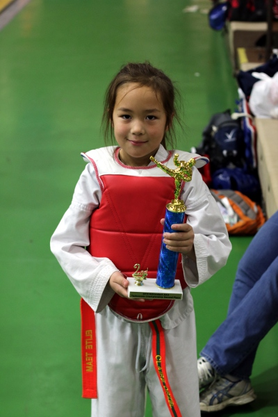 SteelyKid in sparring gear, with her second-place trophy.