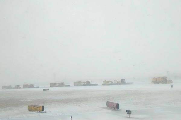 Snow removal trucks on the runway at O'Hare International Airport.