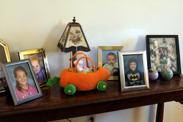 The photo shelf in my parent's living room, with school pictures of the kids.