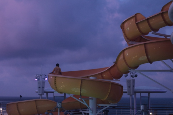 Maintenance workers cleaning and checking one of the waterslides on board.