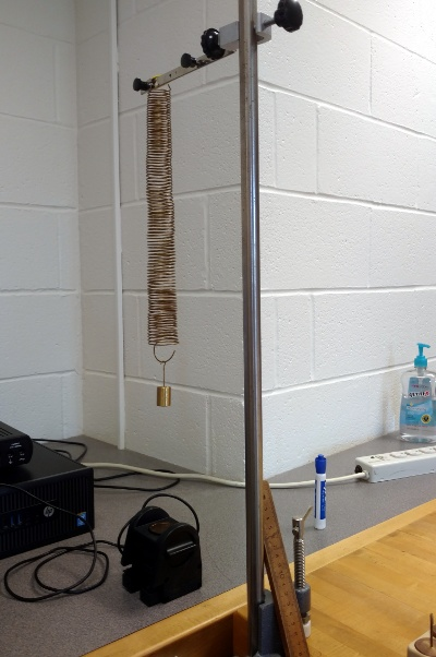 The hanging spring for the lab I'm working on, fortuitously aligned with the corner of the wall behind it.