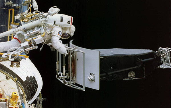 Image credit: NASA, of the first Hubble servicing mission. Astronaut Jeffrey Hoffman removes Wide Field and Planetary Camera 1 (WFPC 1) during change-out operations.