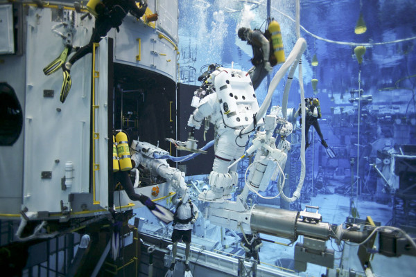 Image credit: NASA. This image shows Hubble servicing Mission 4 astronauts practice on a Hubble model underwater at the Neutral Buoyancy Lab in Houston under the watchful eyes of NASA engineers and safety divers.