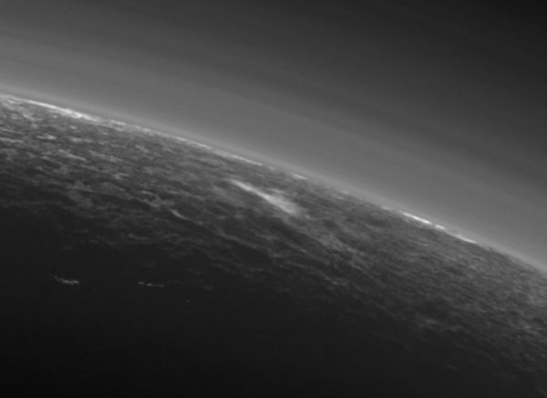 The dark (night) side of Pluto, showcasing layers of atmospheric haze and possible low-lying clouds (foreground) nearer to the surface. Image credit: NASA/JHUAPL/SwRI.