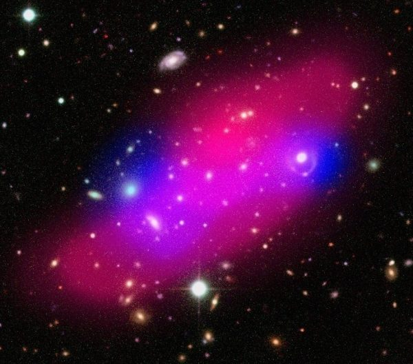 Composite image of the Bullet Group showing galaxies, hot gas (shown in pink) and dark matter (indicated in blue). Dark photons could never explain this gravity alone. Image credit: ESA / XMM-Newton / F. Gastaldello (INAF/IASF, Milano, Italy) / CFHTLS