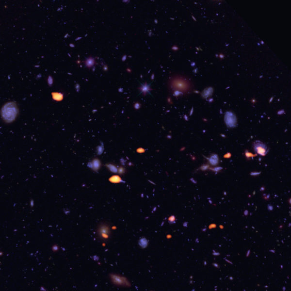 A trove of galaxies, rich in dust and cold gas (indicating star-forming potential) was imaged by ALMA (orange) in the Hubble Ultra Deep Field. Image credit: B. Saxton (NRAO/AUI/NSF); ALMA (ESO/NAOJ/NRAO); NASA/ESA Hubble.