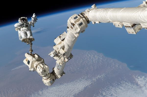 Astronaut Stephen K. Robinson, STS-114 mission specialist, anchored to a foot restraint on the International Space Station's Canadarm2, participates in the mission's third session of extravehicular activity (EVA). Image credit: NASA.