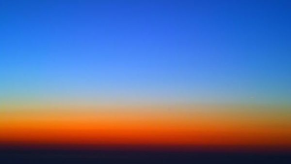 From very high altitudes in the pre-sunrise or post-sunset skies, a spectrum of colors can be seen, but it isn't due to the same rainbow effects you're used to. Public domain image.