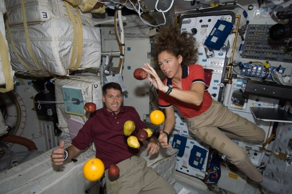 Astronauts, and fruit, aboard the International Space Station. Note that gravity isn't turned off, but that everything -- including the spacecraft -- is uniformly accelerated, resulting in a zero-g experience. Public domain image.