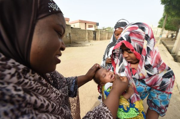 A Nigerian health worker tries to immunise a child during vaccination campaign against polio. The synchronised vaccination campaign, one of the largest of its kind ever implemented in Africa, is part of urgent measures to permanently stop polio on the continent. Image credit: PIUS UTOMI EKPEI/AFP/Getty Images.