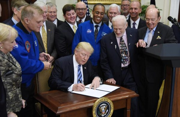 U.S President Donald Trump signs an Executive Order to reestablish the National Space Council as Buzz Aldrin looks on. Image credit: Olivier Douliery-Pool/Getty Images.